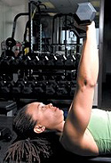 Chelsea Cooper performing flat bench dumbbell chest press. - Copyright – Stock Photo / Register Mark