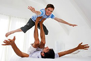 A father using his feet to suspend his young son in the air. - Copyright – Stock Photo / Register Mark