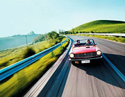 A man and woman cruising along a scenic road in their convertible. - Copyright – Stock Photo / Register Mark