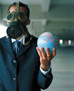Man wearing gas mask holds the Earth in his hand. - Copyright – Stock Photo / Register Mark